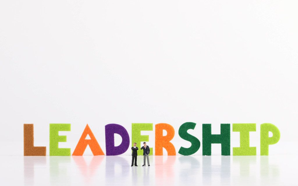 The word Leadership with two businessman on white background