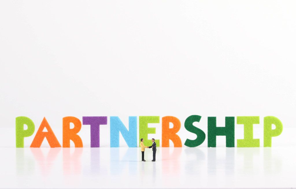 The word Partnership with two businessman shaking hands on white background