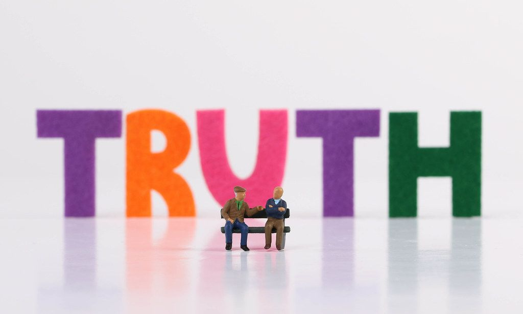 The word Truth with two seniors sitting on bench on white background