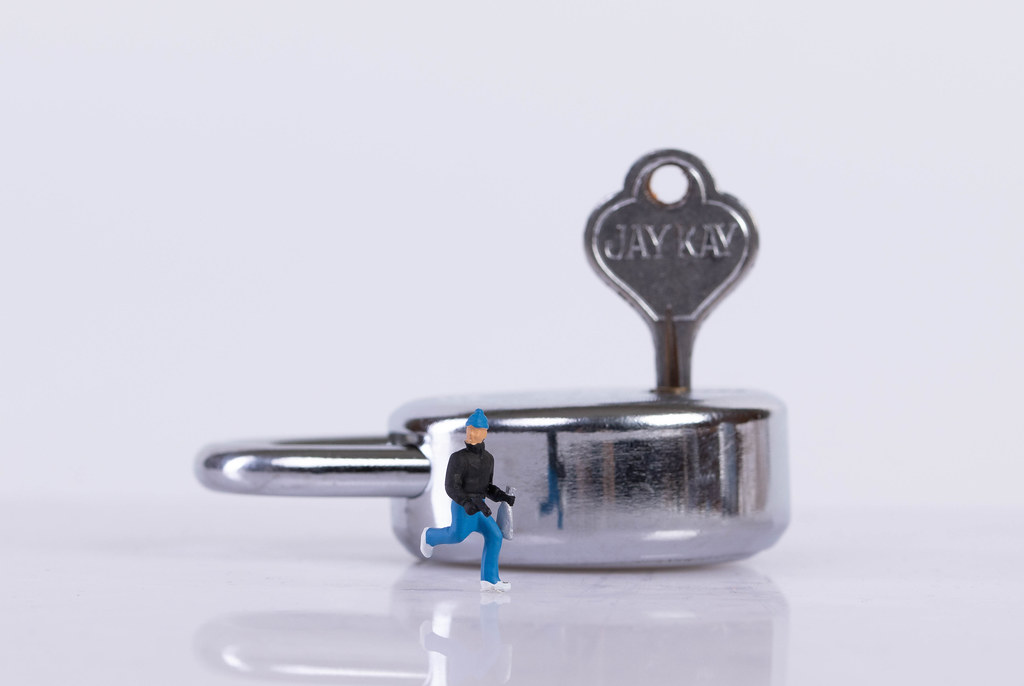 Thief and padlock on white background