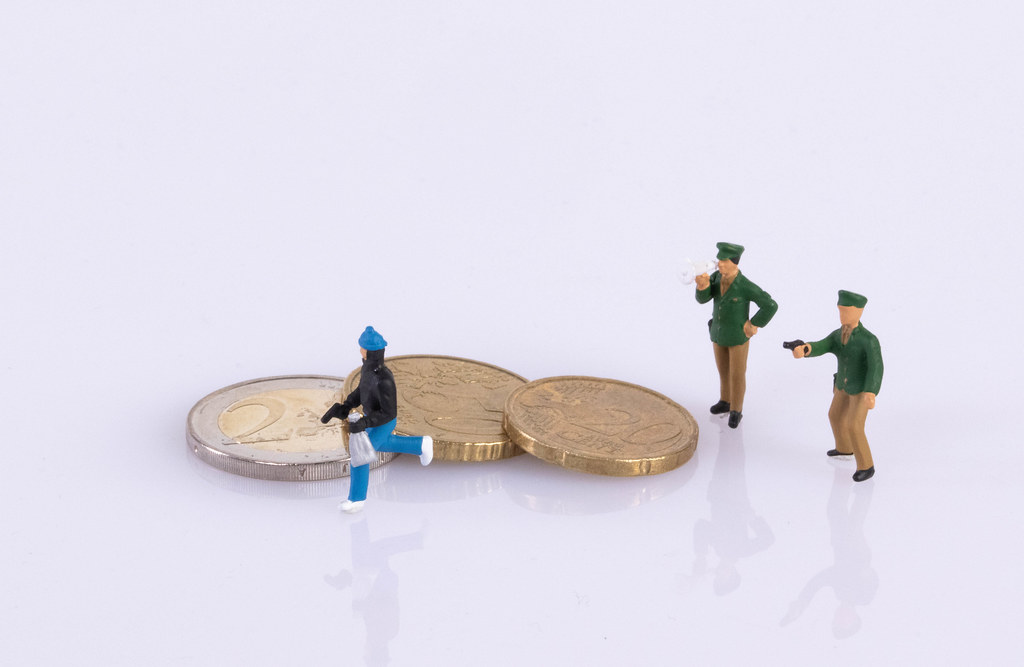 Thief and police with coins on white background