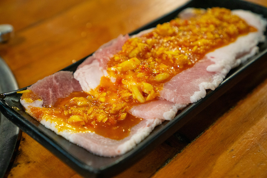 Thin Raw Pork Slices topped with Sauce and Garlic on a Black Ceramic Plate at a Barbecue Restaurant