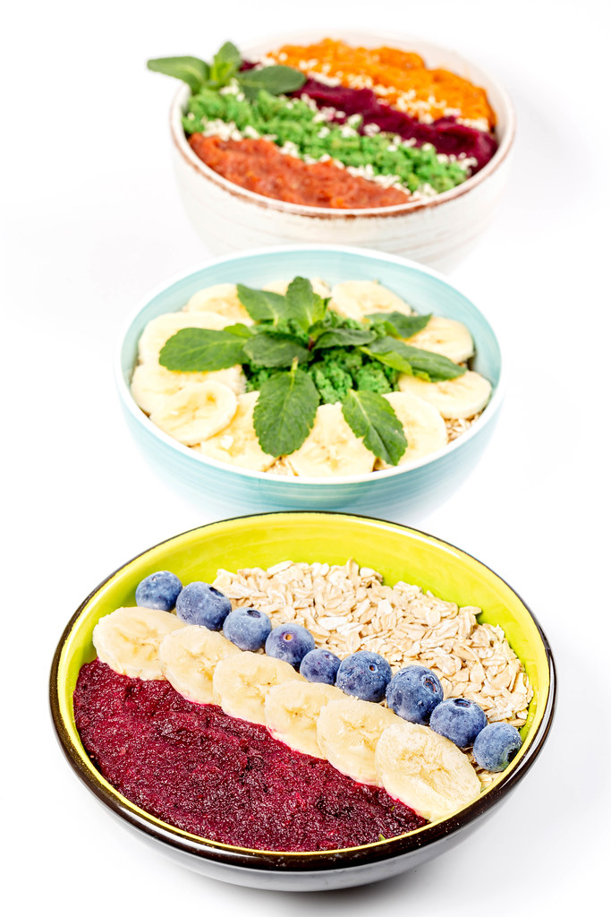 Three bowls with oatmeal and fruits on white