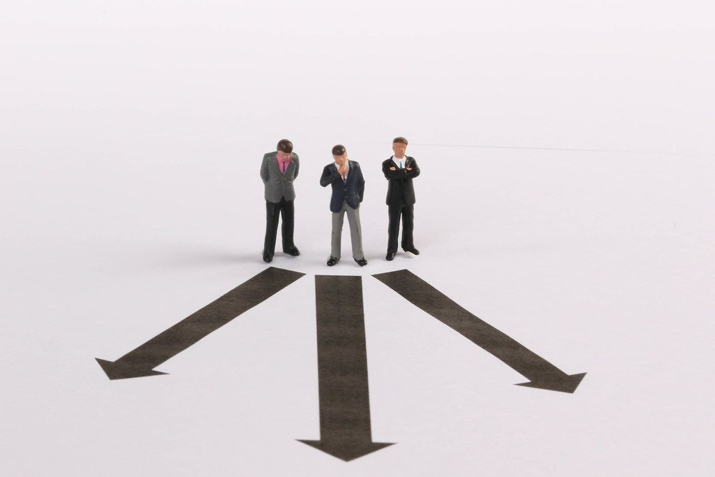 Three businessman in front of decision which way to choose
