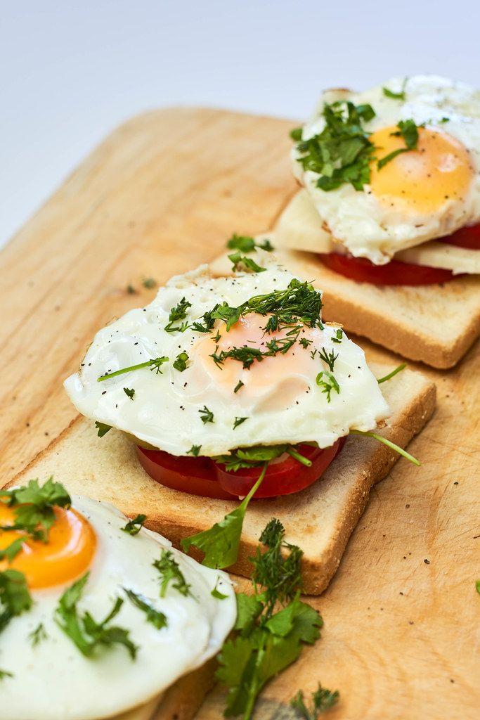 Three delicious fried eggs on toast for breakfast