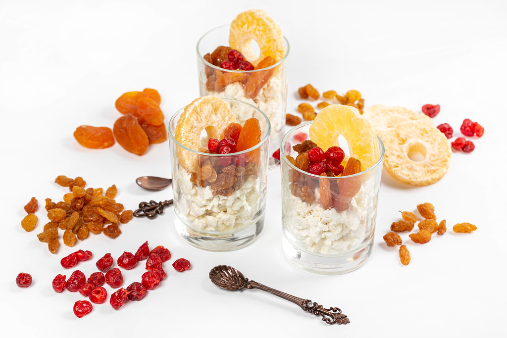 Three glasses with cottage cheese and dried fruits on a white background with spoons