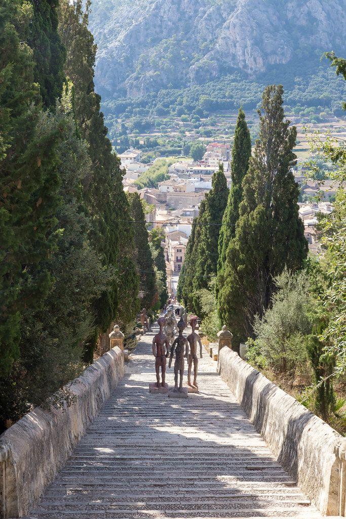 Three human figures sculpted by Joan Bennàssar, standing on the Carrer del Calvari steps in Pollença