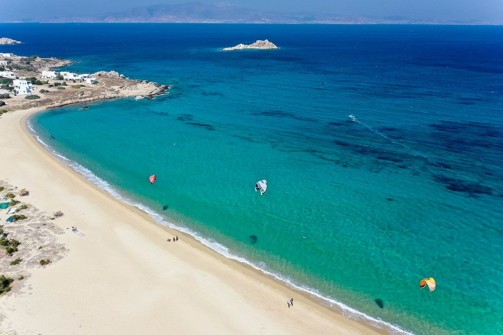 Three kites flying in the wind on the empty beach of Mikri Vigla on the Greek island of Naxos. Aerial view