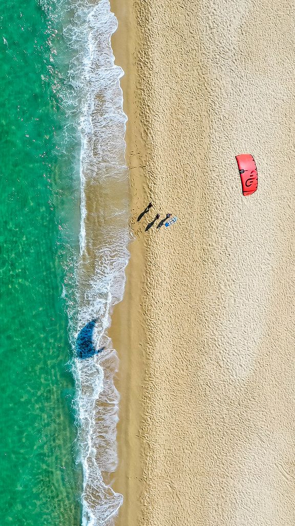 Three people fly a red kite on a sandy beach. Windy beach of Mikri Vigla, Naxos. Overhead drone shot