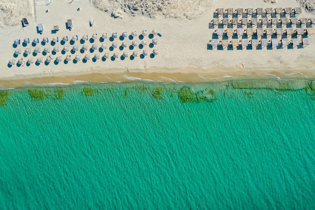 Three rows of round thatched beach umbrellas and four rows of square sunshades. Plaka beach, Naxos