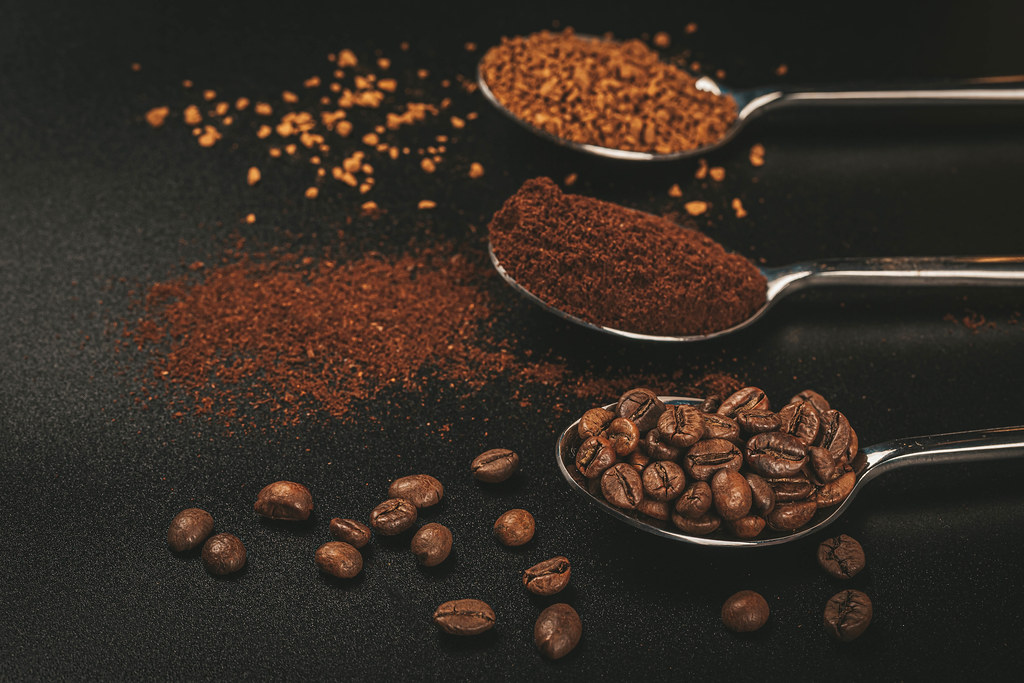 Three spoons of coffee with Soluble coffee, coffee beans and ground coffee on dark background