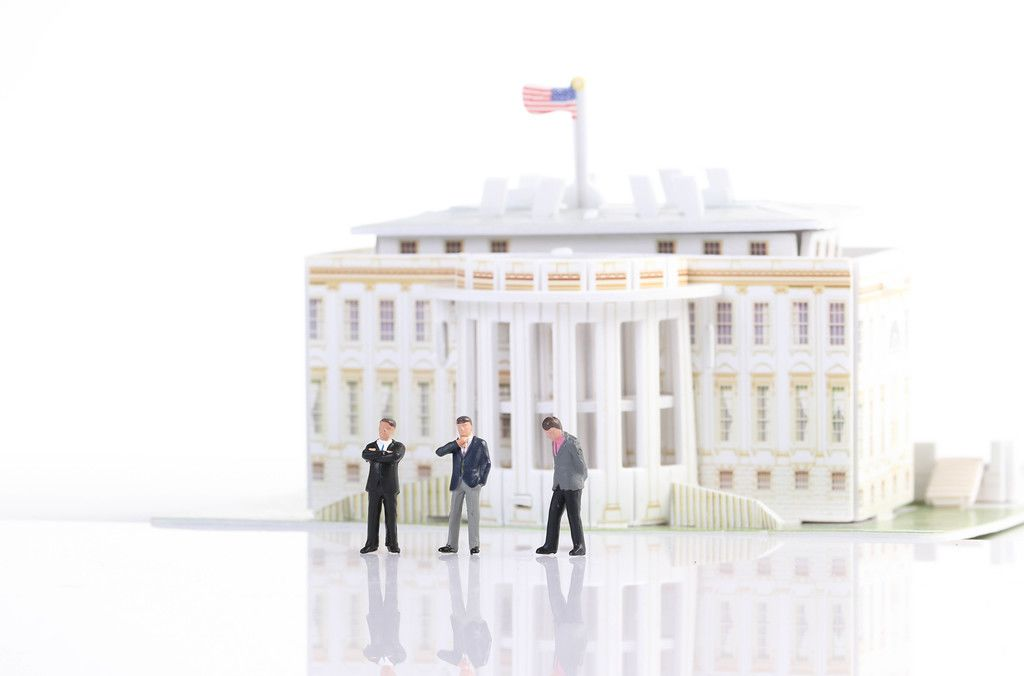Three suited businessman standing in front of White House