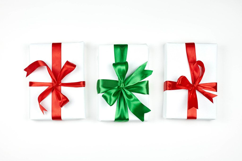 Three white X-mas gifts with red and green textile ribbon on white background