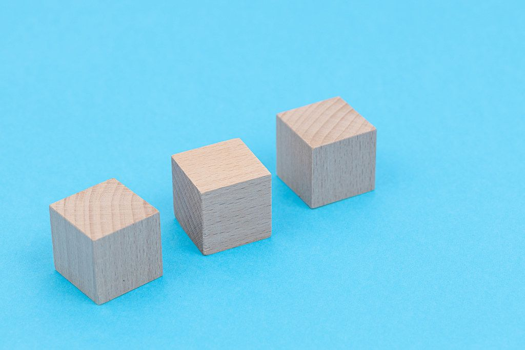 Three Wooden Cubes above blue background with copy space