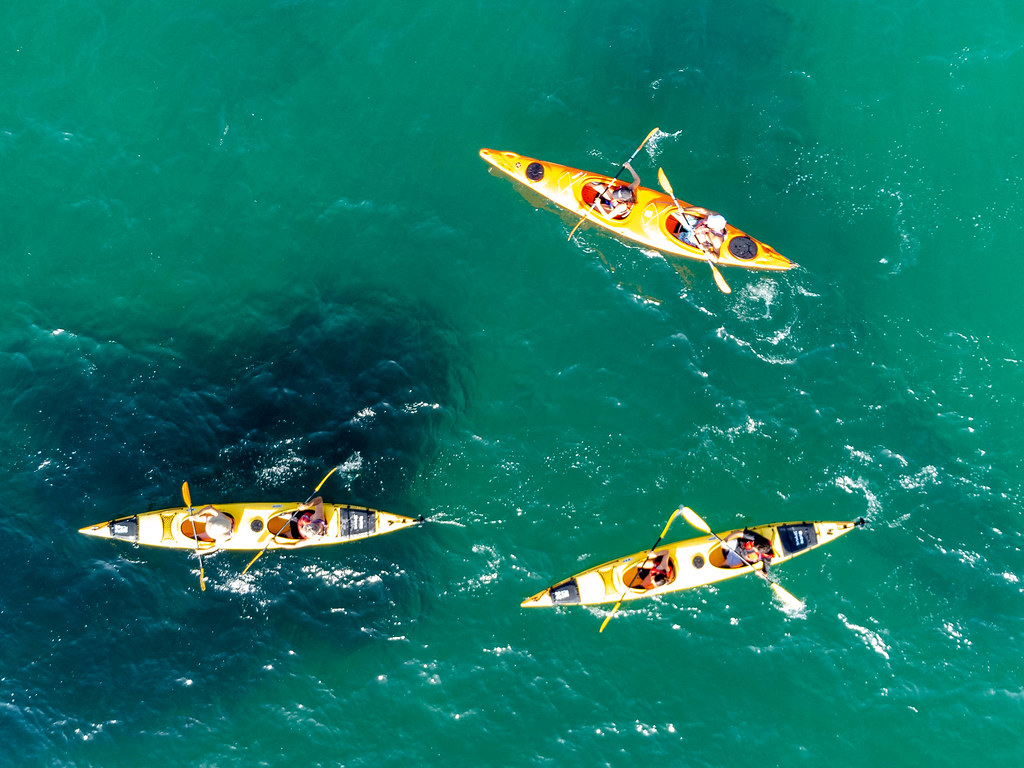 Three yellow kayaks with two people each on board in the waters of Kastani Beach at Skopelos. Drone photo
