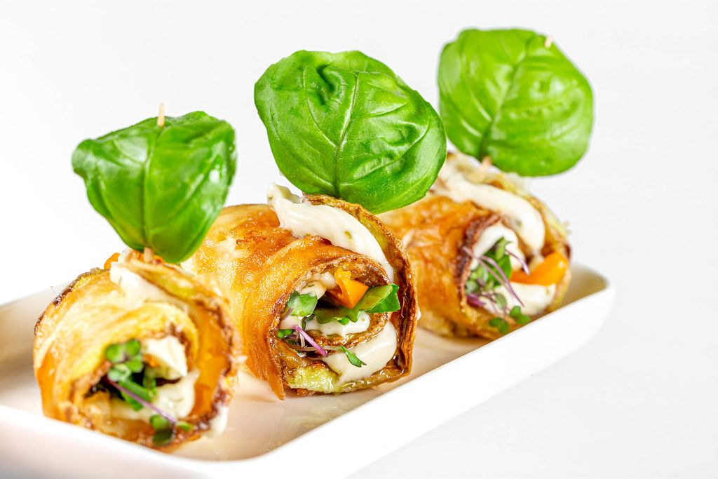 Three zucchini rolls with vegetables, sauce and basil leaves on a white plate