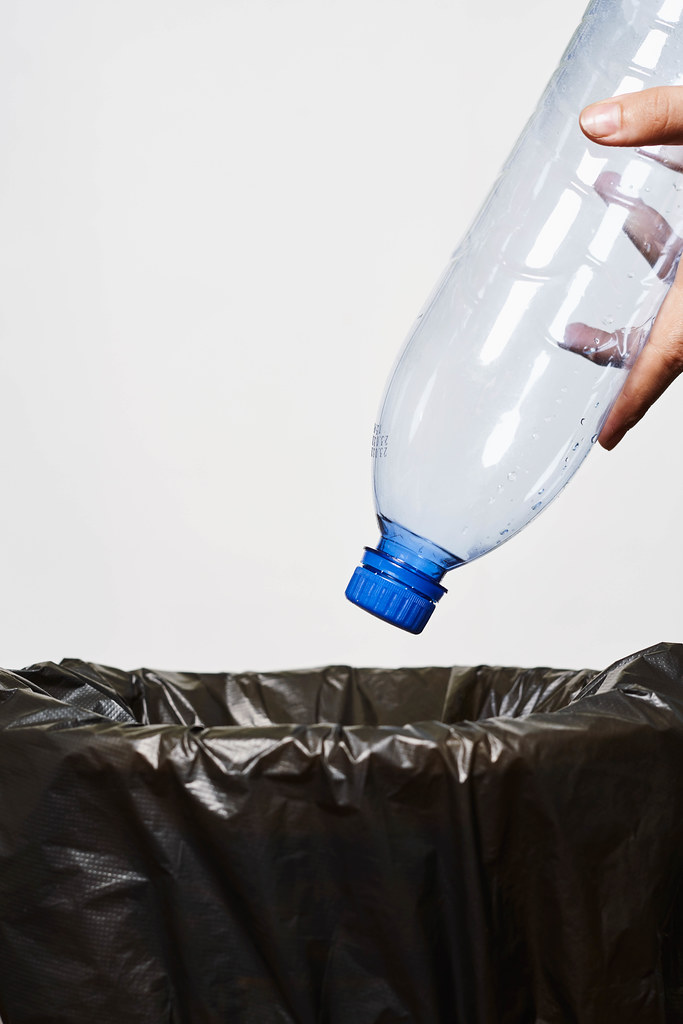 Throwing a plastic bottle into trash can