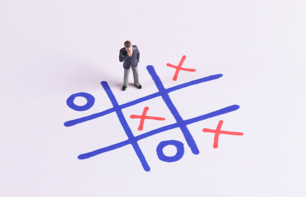 Tic Tac Toe game and miniature businessman on white paper