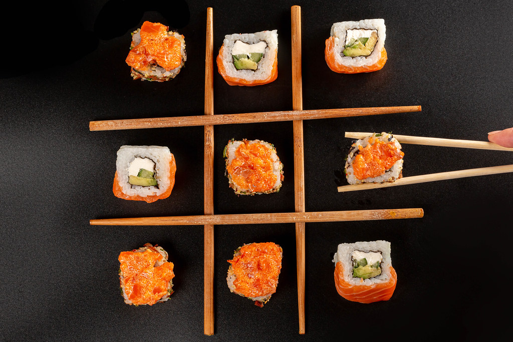 Tic-tac-toe game concept, sushi with chopsticks on black background