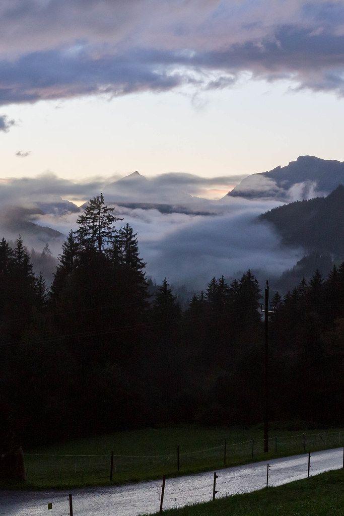 Tiefhängende Wolken im Wald mit Bergen am Horizont: Alpenlandschaft in Tirol, Österreich