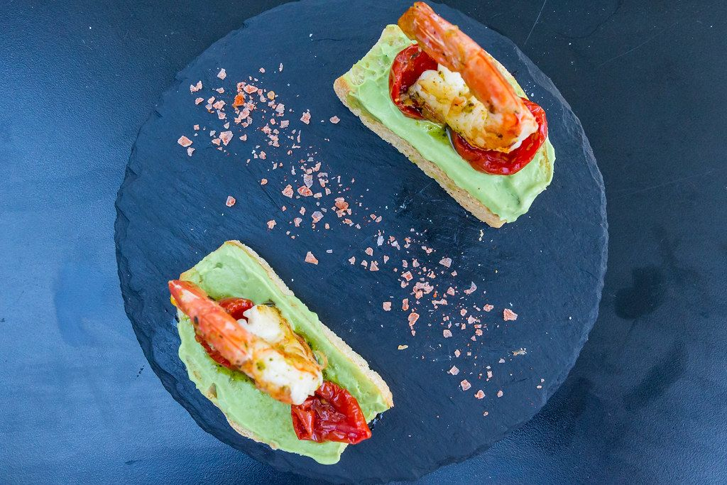 Toasted bread with king prawns, avocado creme sauce and dried tomatoes at Q11, Pollença. Top view