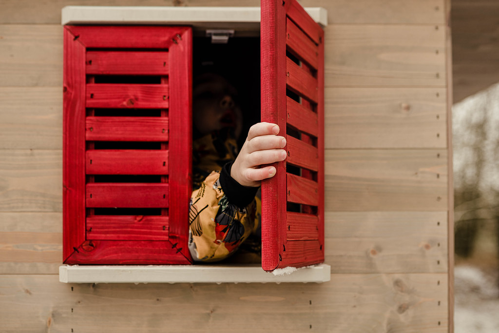 Toddler Playing With Red Windows