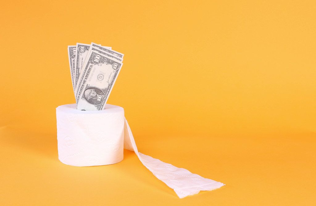 Toilet paper with dollar banknotes on orange background