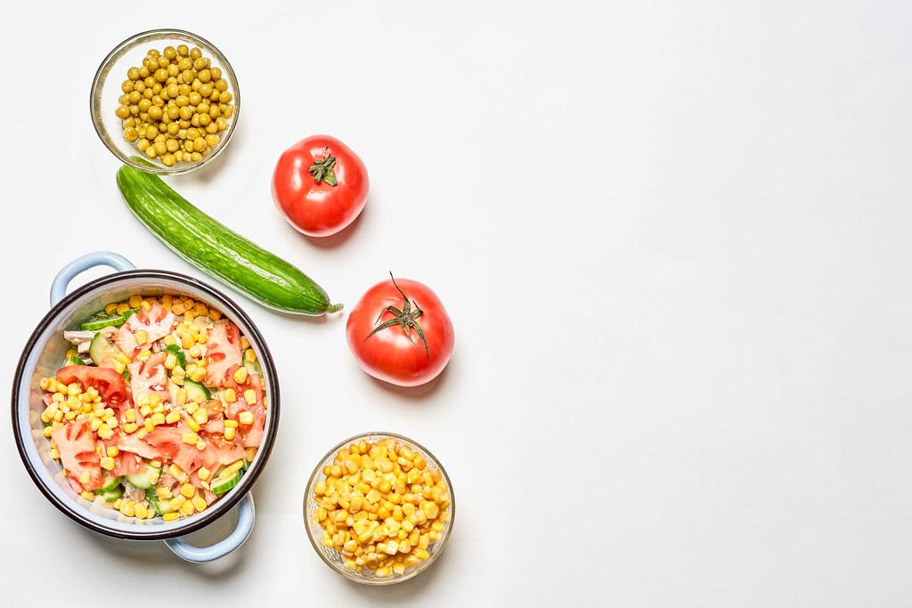 Tomaten, Gurke, Topf und Schalen mit Mais und Erbsen auf weißem Hintergrund mit Platz für Text