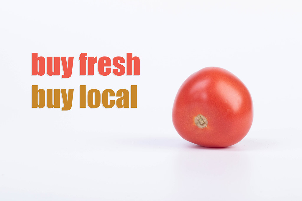 Tomato with Buy fresh Buy local text on white background