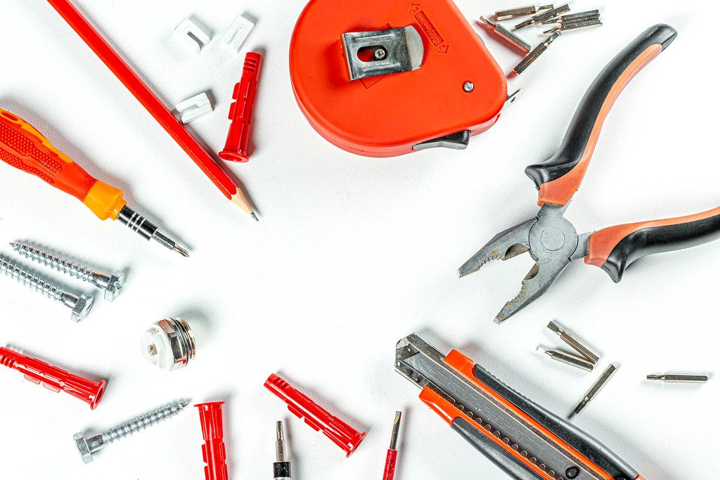 Tools and screws on white background, top view