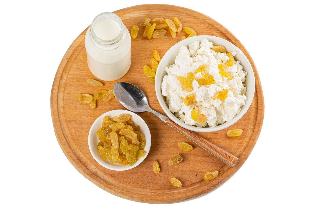 Top view, a bowl of cottage cheese with raisins on a wooden round board with milk