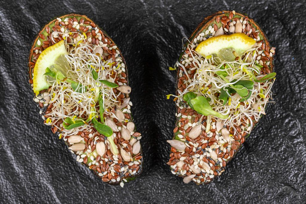 Top view, avocado with a mix of seeds and micro greens