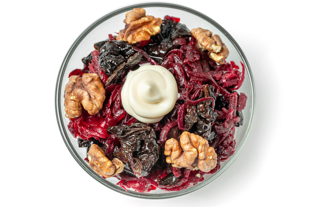 Top view, beetroot salad with walnuts and prunes