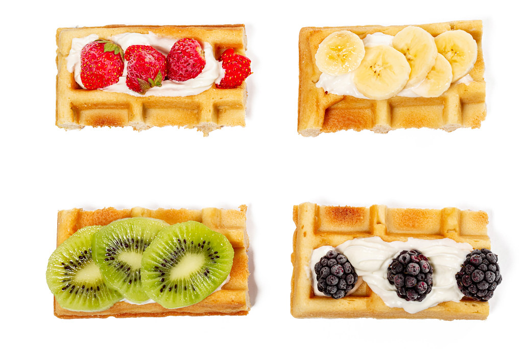 Top view, belgian waffles with strawberries, kiwi, banana and blackberries