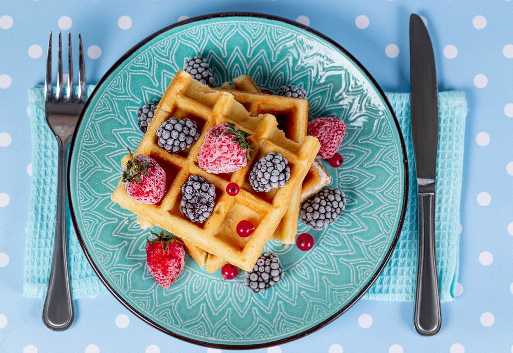 Top view, Belgian waffles with strawberries, red currants and blackberries on a blue background