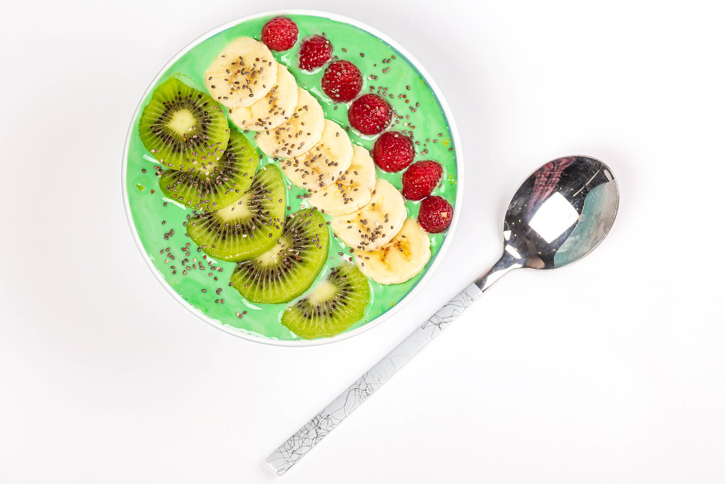 Top view, bowl of oatmeal with yogurt and fruits on white background