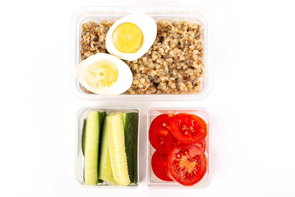 Top view, buckwheat with boiled eggs, cucumbers and tomatoes in plastic containers