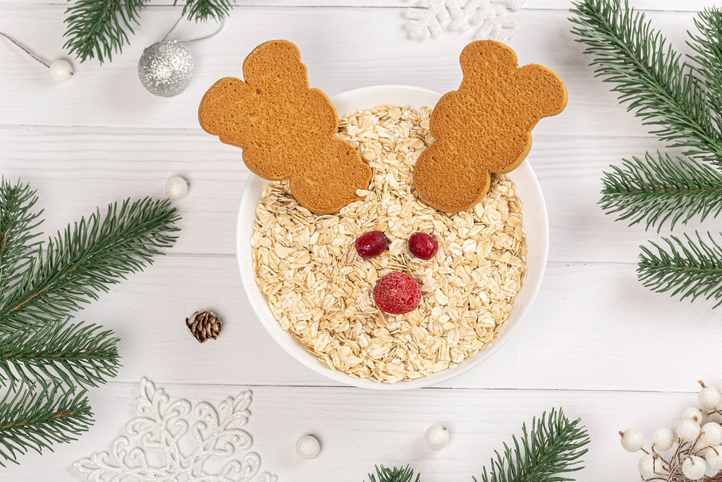 Top view, christmas breakfast in the form of a reindeer made of oatmeal and cookies