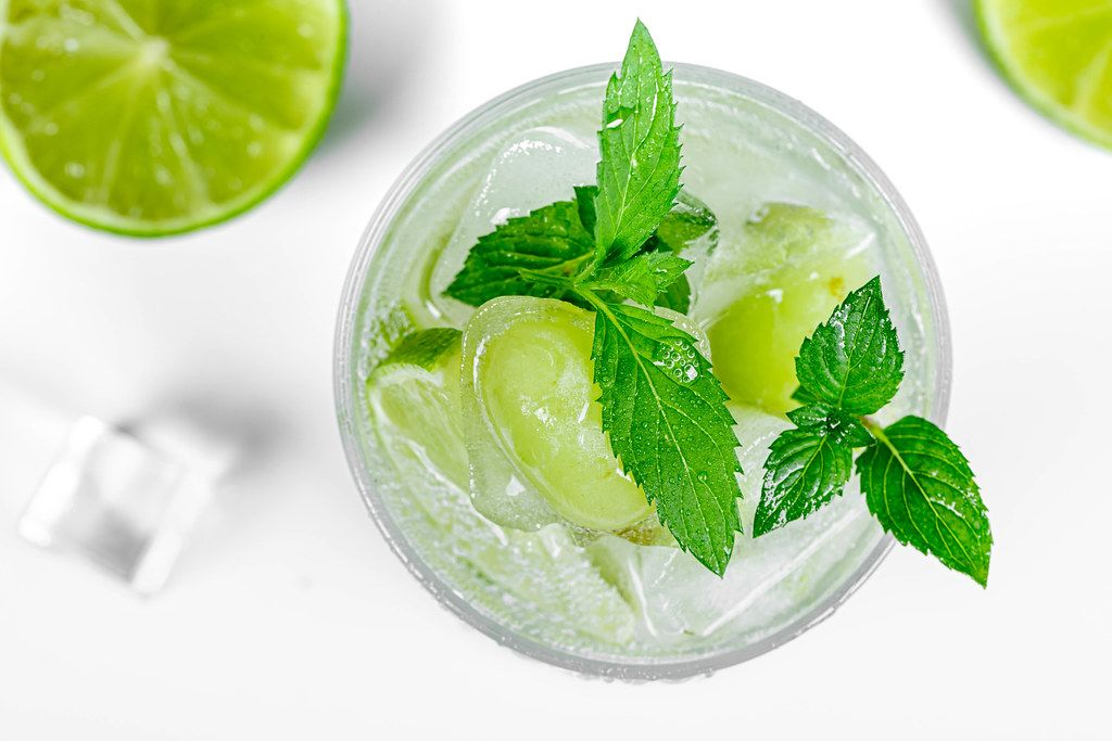 Top view, cold cocktail with ice, frozen lime, grapes and fresh mint