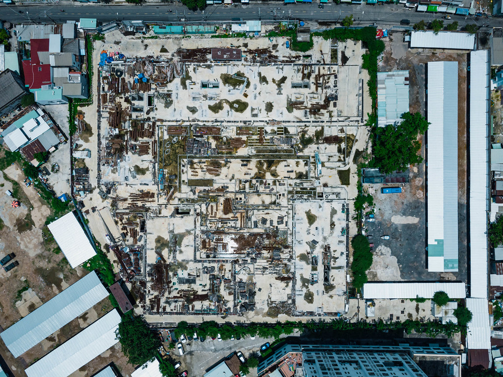 Top View Drone Photo of a Large Construction Side next to a Street with many Materials laying around in Ho Chi Minh City, Vietnam