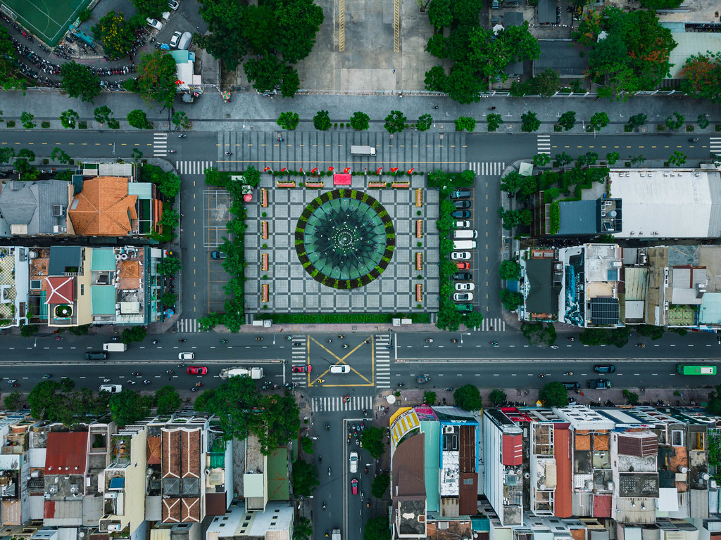 Top View Drone Photo of Traffic on the Streets around a Square with Water Fountain at the Kahnh Hoi Public Park in District 4 in Ho Chi Minh City, Vietnam