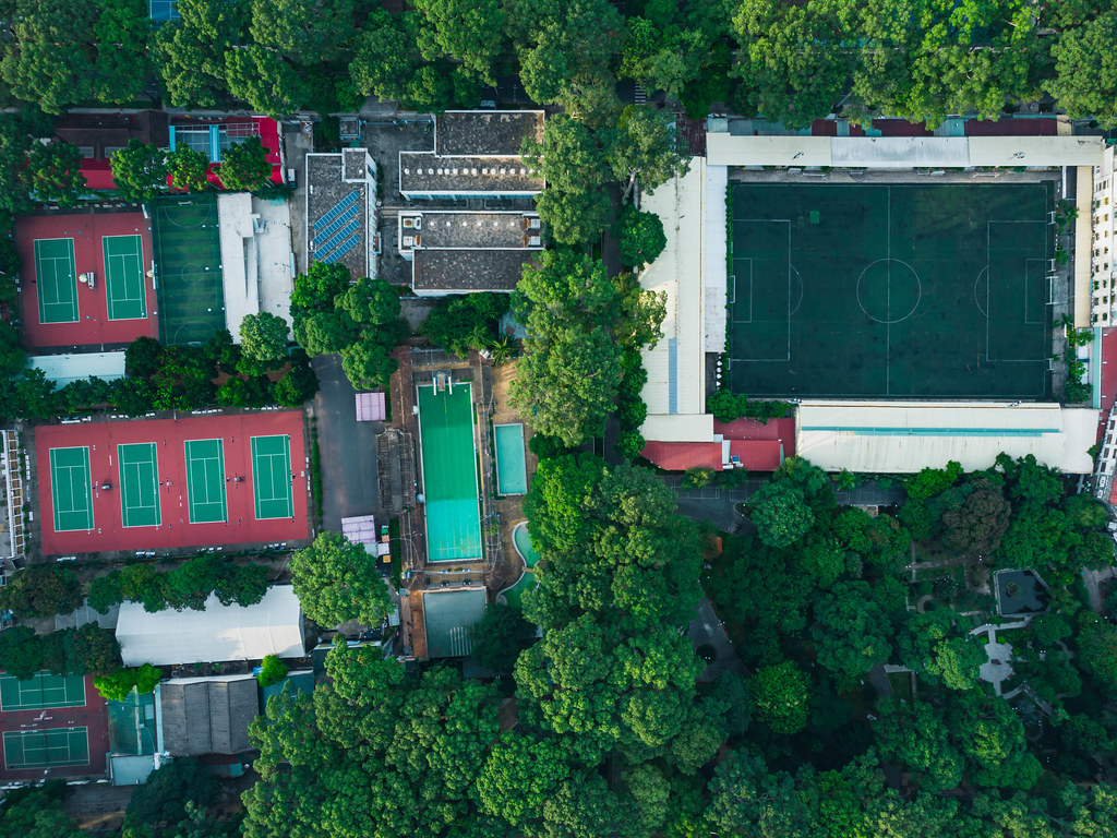 Top View Drone Shot of a Sports Facility with several Tennis Courts, Swimming Pool, Football Stadium surrounded by Tao Dan Park in Ho Chi Minh City, Vietnam