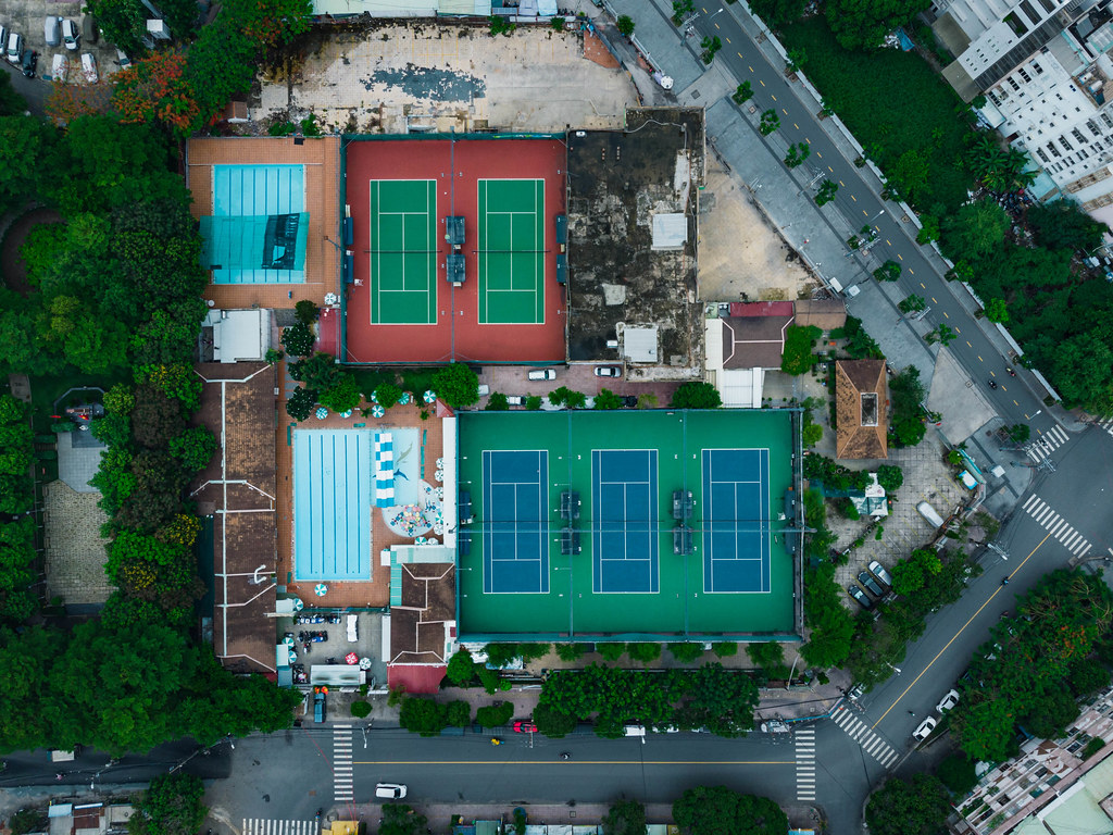 Top View Drone Shot of different colored Tennis Courts with Hardcourt Surface and Swimming Pools next to a Street in District 4 in Ho Chi Minh City, Vietnam