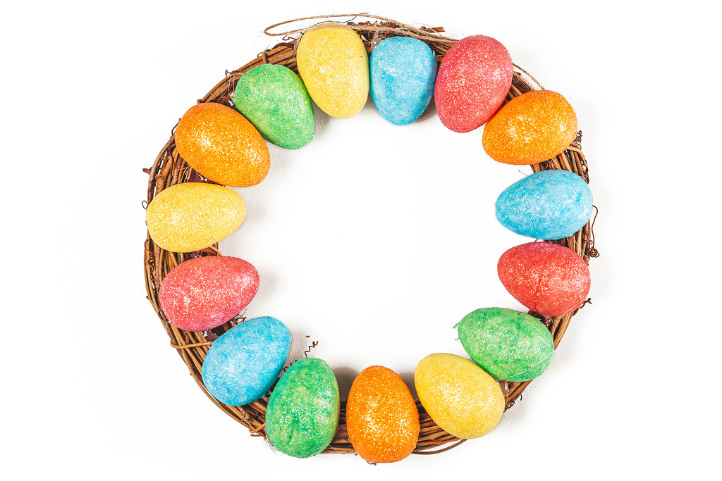 Top view, easter round wreath with colorful eggs