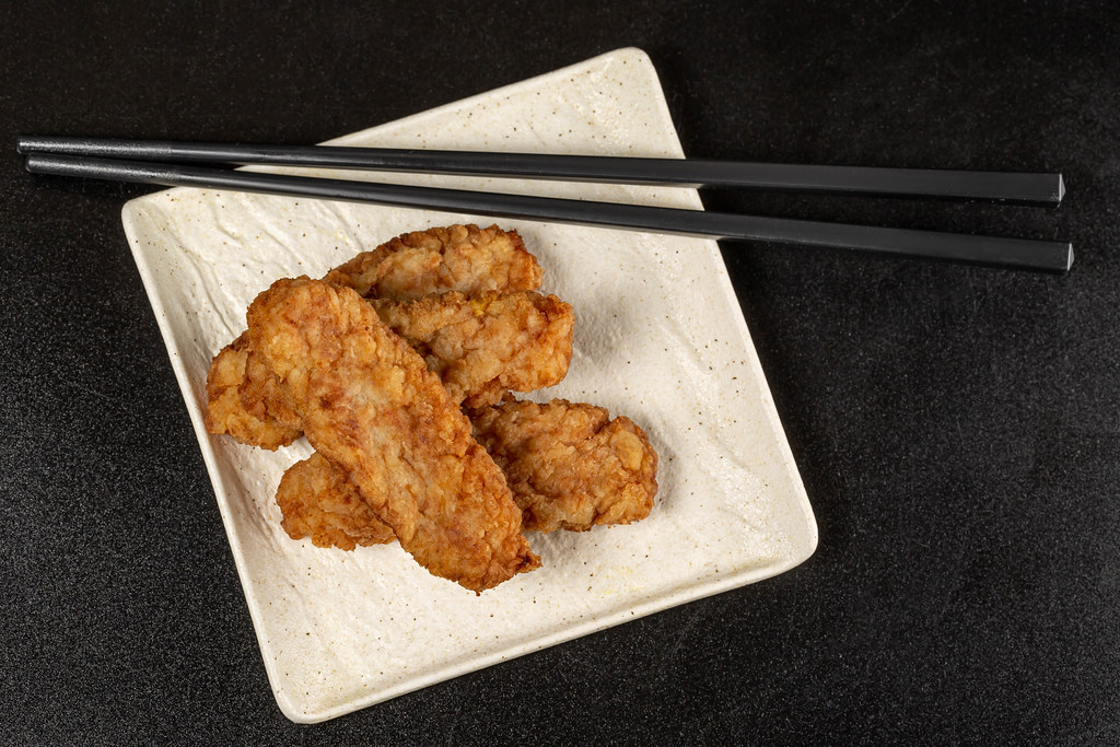 Top view, fish fillet cutlets with chopsticks on dark background