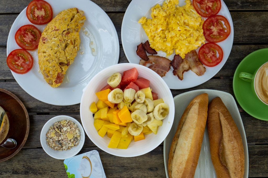 Top View Food Photo of Breakfast Table with Mixed Fruit Salad, Muesli with Yogurt, Omelette with Bacon and Tomatoes,  Scrambled Eggs with Bacon Strips, Baguettes and Coffee