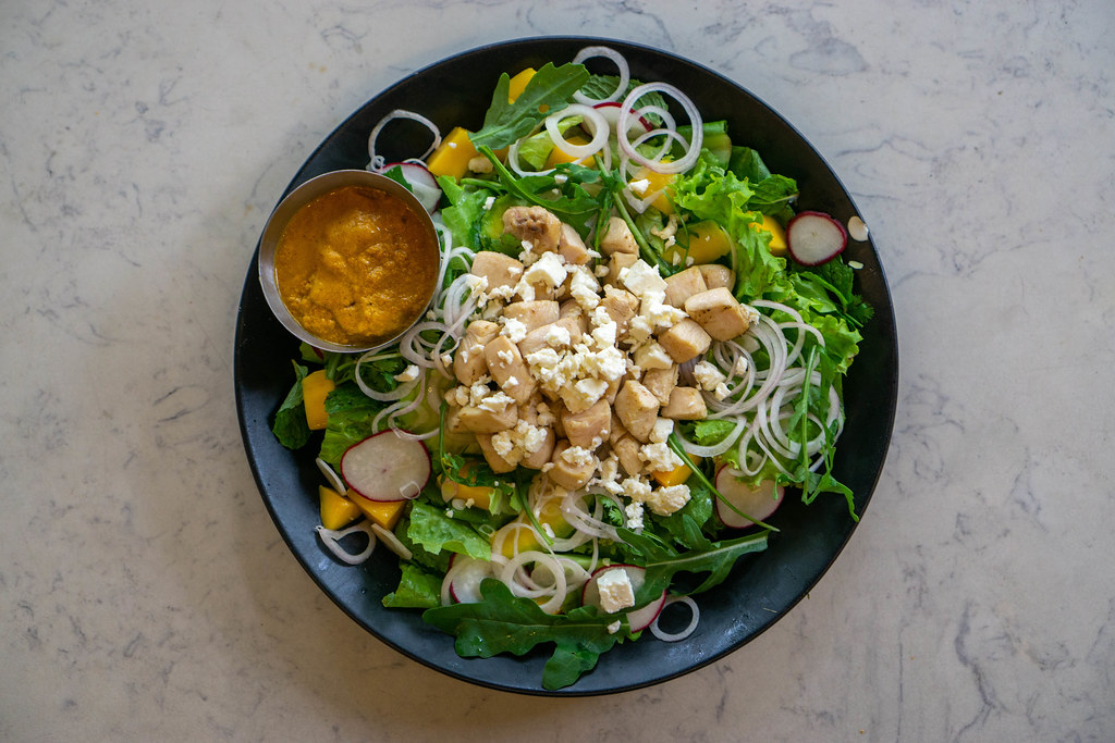 Top View Food Photo of Curry Mango Chicken Salad with Arugula, Feta Cheese and Onions on a Plate at a Restaurant