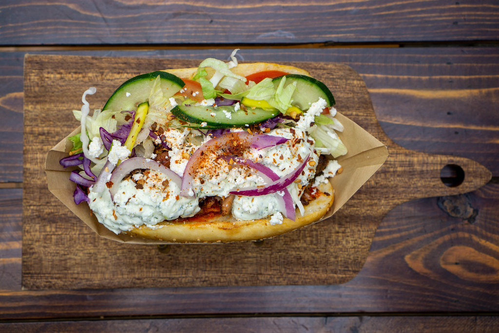 Top View Food Photo of Doner Kebab with Fresh Vegetables, Mixed Meat, Tzatziki, Feta Crumble and Chili on a Wooden Board