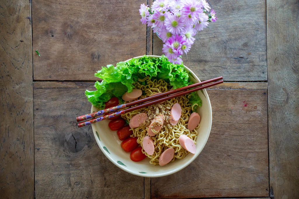 Top View Food Photo of Dried Instant Noodles with Sausages, Cherry Tomatoes, Peanuts and Lettuce on a Wooden Table with Flowers
