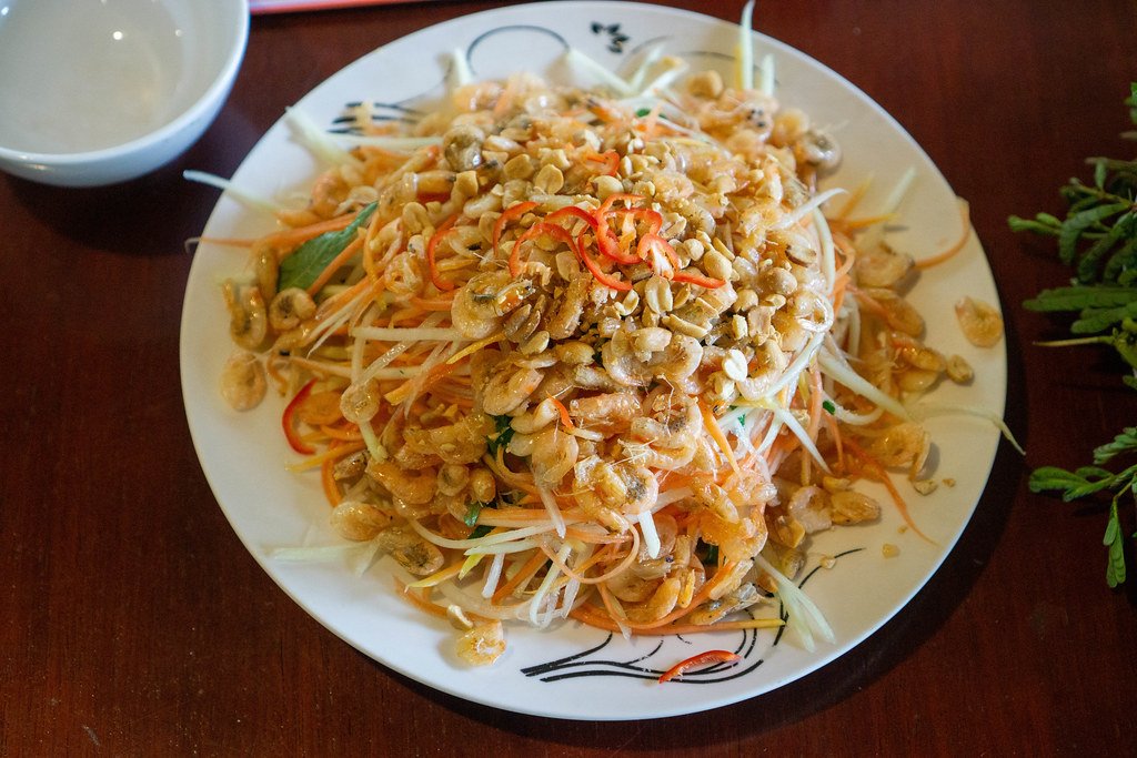 Top View Food Photo of Fresh Papaya Salad with Dried Shrimps, Herbs and Chili on a Wooden Table in a Restaurant in Can Tho, Vietnam